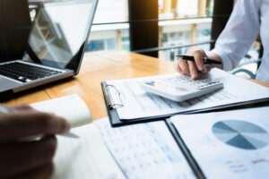 Income tax planning and preparation using a calculator at a workplace, wealth concept